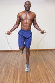 Shirtless muscular man skipping in gym — Stock Photo
