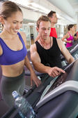 Trainer talking to his client on the treadmill — Stock Photo