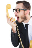 Geeky businessman shouting at telephone — Stock Photo