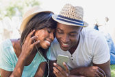 Happy couple lying in garden together listening to music — Stockfoto