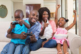 Family relaxing on the couch playing video games — Stock Photo
