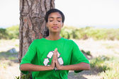 Pretty environmental activist doing yoga by a tree — Stock Photo