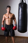 Muscular boxer with punching bag in gym — Stock Photo