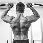 Male body builder doing pull ups at the gym — Foto Stock