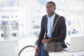 Thoughtful businessman with his bicycle  — Stock Photo