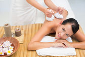 Peaceful brunette enjoying a herbal compress massage — Stock Photo