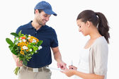 Happy flower delivery man with customer — Stock Photo