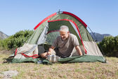 Happy camper cooking on camping stove outside his tent — Stock Photo