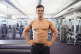 Smiling shirtless muscular man with hands on hips in gym — Stock Photo