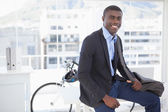 Smiling businessman with his bicycle  — Stock Photo