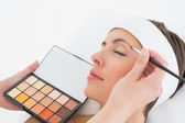 Hand applying eyeshadow to beautiful woman — Stock Photo