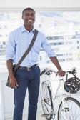Happy businessman standing with his bike — Stockfoto