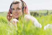 Pretty blonde lying on grass listening to music — Stockfoto