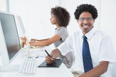 Young designer smiling at camera at his desk — Stock Photo