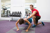 Personal trainer with client doing push up on exercise ball — ストック写真