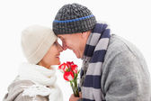 Happy mature couple in winter clothes with roses — Stock Photo