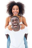 Casual man giving his smiling girlfriend a piggy back — Stock Photo