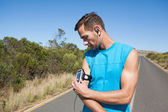 Athletic man adjusting his music player on a run — Stock Photo