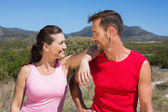 Active couple standing on country terrain smiling at each other — Stock Photo