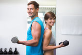 Fit couple lifting dumbbells together smiling at camera — Foto Stock