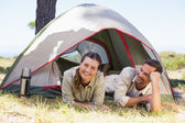 Outdoorsy couple smiling at camera inside their tent — 图库照片