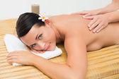 Peaceful brunette enjoying a back massage smiling at camera — Stock Photo
