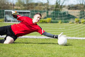 Goalkeeper in red saving a goal during a game — Стоковое фото