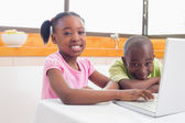 Cute siblings using laptop together — Stock Photo