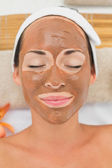 Smiling brunette getting a mud treatment facial — Stock Photo