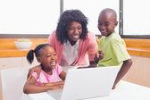 Schattig broers en zussen met behulp van laptop samen met moeder — Stockfoto