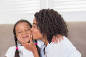 Pretty mother sitting on the couch with her daughter kissing her — Stock Photo