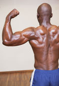 Rear view of shirtless muscular man flexing muscles — Stock Photo