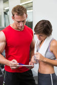 Handsome personal trainer with his client looking at clipboard — Stock Photo