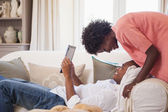 Happy couple relaxing on the couch with tablet pc — Stock Photo
