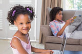 Cute daughter using laptop at desk with mother on couch — Stock Photo
