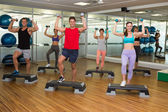 Fitness class doing step aerobics with dumbbells — Stock Photo