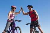 Fit cyclist couple standing at the summit high fiving — Stockfoto