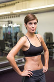 Fit brunette in black sports bra looking at camera — Stock Photo