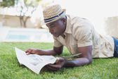 Smiling man relaxing in his garden reading newspaper — Stock Photo
