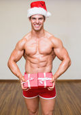 Shirtless macho man in santa hat holding gifts — Stock Photo