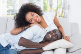Attractive couple cuddling on the couch — Stockfoto