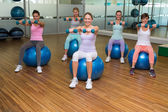 Fitness class holding dumbbells on exercise balls in studio — Stok fotoğraf