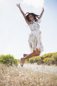 Happy pretty woman jumping up in floral dress — Stock Photo