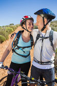 Active couple embracing on a bike ride in the country — Stok fotoğraf