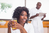 Pretty woman in bathrobe having juice — Stock Photo