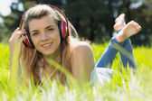 Pretty blonde lying on grass listening to music — Stock Photo