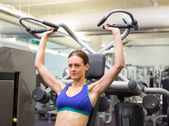 Fit focused brunette using weights machine for arms — Stock Photo