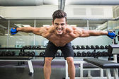 Smiling shirtless bodybuilder with arms outstretched in gym — ストック写真