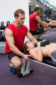 Personal trainer helping client lift dumbbells — Stockfoto