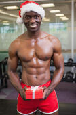 Shirtless macho man in santa hat holding gift — Stok fotoğraf